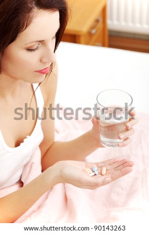 Site view of a beautiful young woman in bed, holding pills and a glass of water.