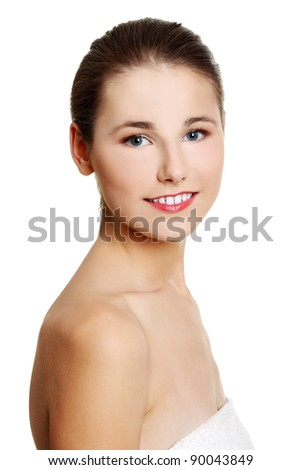 Site view portrait of a young beautiful female caucasian teen being wrapped with a towel, smiling to the camera, on white.