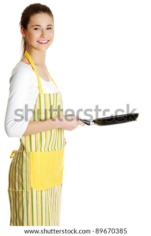 Site view portrait of a young smiling caucasian female teen dressed in apron, holding a frying pan in front of her, on white. - stock photo