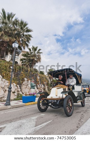 "SITGES, SPAIN - MARCH 27: Jacques Pilla drives a 1909 Renault AX to Sitges Port for the second phase of the ""53rd Rally of Ancient Cars Barcelona-Sitges"" on March 27, 2011 in Sitges, Spain. - stock photo"