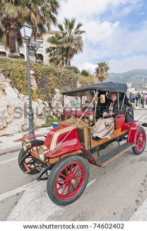"SITGES, SPAIN - MARCH 27: Victor Buil drives a 1910 Renault 2 Cil to Sitges Port for the second phase of the ""53rd Rally of Ancient Cars Barcelona-Sitges"" on March 27, 2011 in Sitges, Spain. - stock photo"