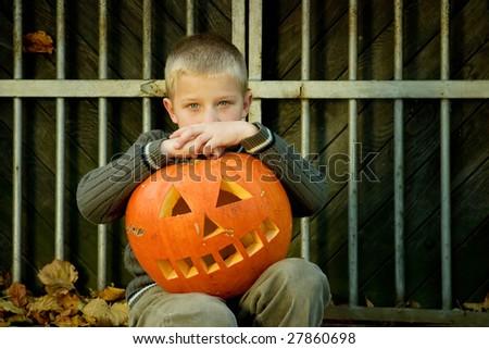 Siting little boy with halloween pumpkin - stock photo