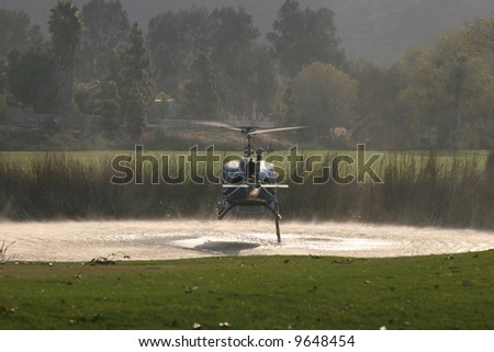 Sitting above the lake, the Sherriff's helicopter sucks in water - stock photo