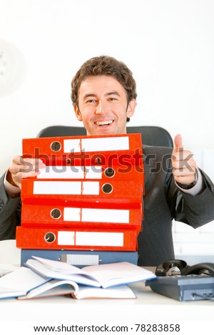 Sitting at office desk smiling modern businessman looking out from pile of folders and showing thumbs up gesture