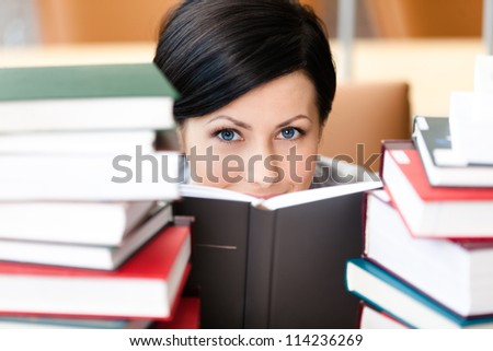 Sitting at the desk student looks out over the book. Training process - stock photo