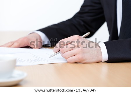 Sitting at the table business man making notes in the making notes pad