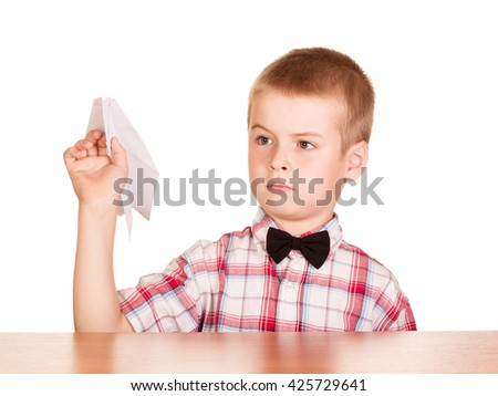 Sitting at the table pretty boy with paper plane in the hand on a white background. - stock photo