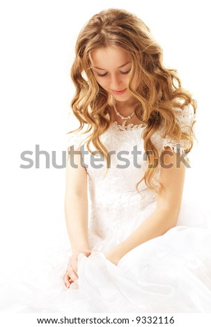 sitting beauty bride in white dress looks down over white - stock photo