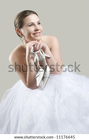 sitting beauty bride in white dress with shoes in her hands