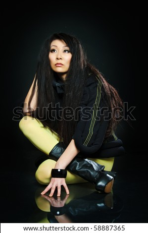 sitting brunette asian model on black background with night reflections