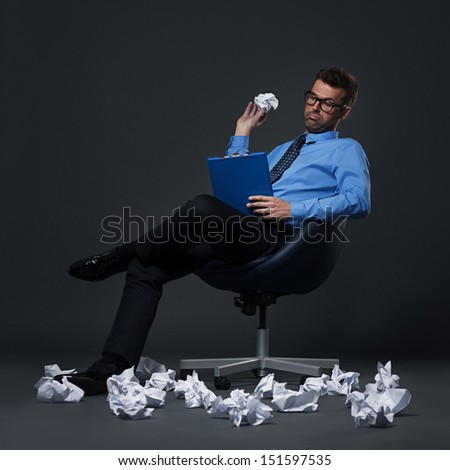 Sitting businessman throwing a crumpled paper with bad ideas on the floor - stock photo