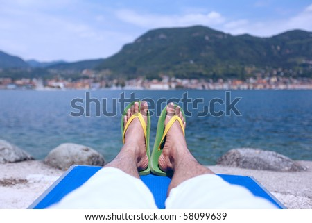 Sitting by the lakeside enjoying the sun - stock photo