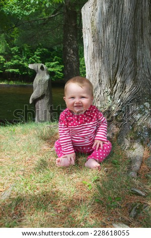 Sitting by the tree the baby is happy to relax in the shade - stock photo