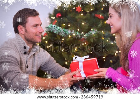 Sitting couple giving each other presents against fir tree forest and snowflakes - stock photo
