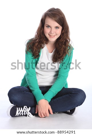Sitting cross legged on floor a beautiful high school teenager girl with long brown hair wearing blue jeans and green jumper with big happy smile. Studio shot against white background.