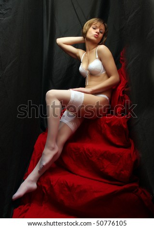 Sitting flirty girl with long slim legs in white nylons. Vintage style low key photography. - stock photo
