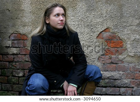 sitting girl in black clothing on brick wall background