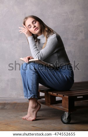 Sitting girl with book touching her face. Gray background
