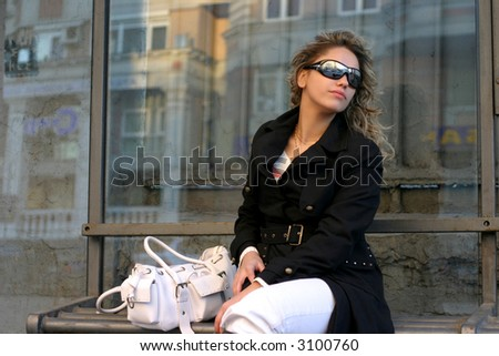 sitting girl with sunglasses and white handbag on stop
