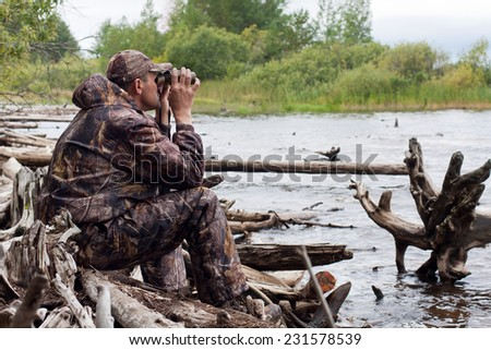 sitting hunter with binoculars - stock photo