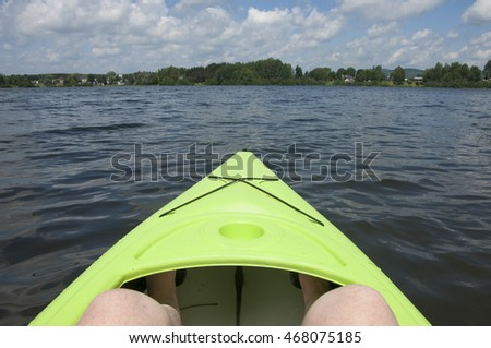 Sitting in a green kayak on a calm lake in the summer sun, point of view from the kayak.  Lac de Source in Quebec, Canada near Montreal.  Vacation homes and trees on the other side of the lake.
