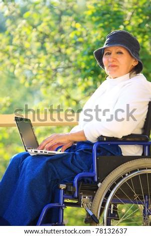 Sitting In Wheelchair Using Laptop - stock photo