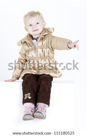 sitting little girl wearing jacket - stock photo
