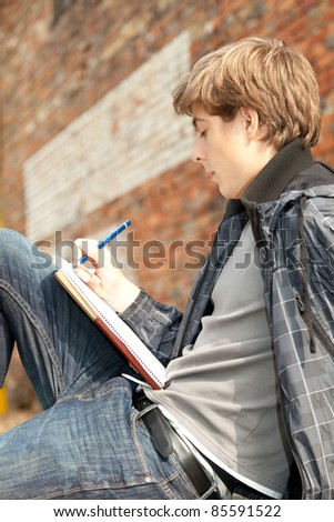 sitting male student learning near the brick wall - stock photo