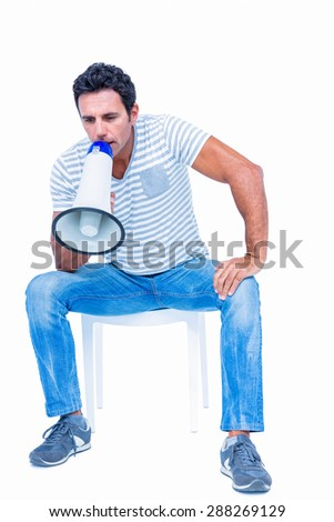 Sitting man shouting through megaphone on white background - stock photo