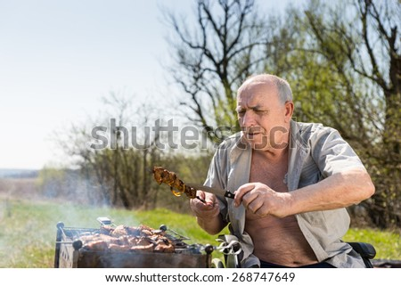 Sitting Old Man Checking if Grilled Meat on a Stick are Well-Cooked While Doing a Barbecue at the Park. - stock photo