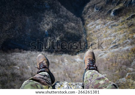 Sitting on a cliff - stock photo