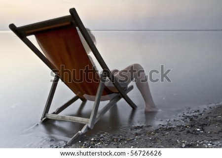 sitting on a deckchair at sunset - stock photo