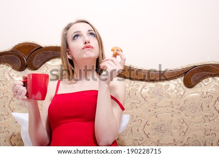 sitting on bed or coach in red dress drinking tea and eating cake beautiful blonde young woman having fun looking up at copy space closeup portrait picture - stock photo