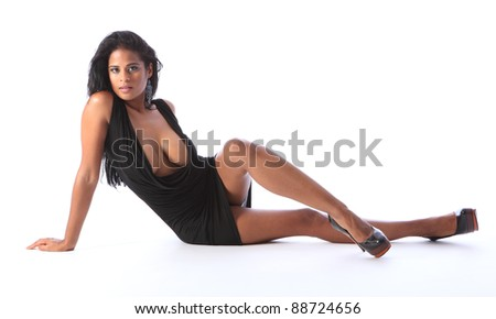 Sitting on floor a young beautiful african american fashion model wearing short black dress and stiletto heels, showing off long legs big boobs and cleavage. - stock photo