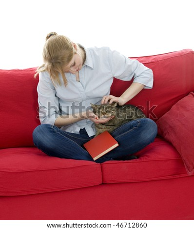 sitting on red sofa young woman with book strokes grey cat - stock photo