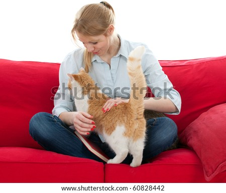 sitting on red sofa young woman with  cat - stock photo
