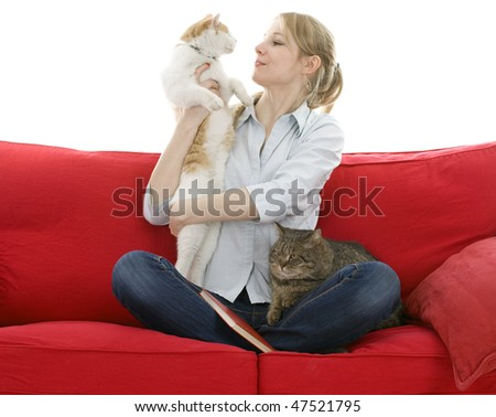 sitting on red sofa young woman with two cats - stock photo
