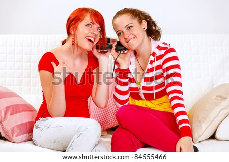 Sitting on sofa two girlfriends holding headphones and listening music - stock photo