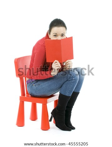 sitting on the child's chair young woman reading book - stock photo