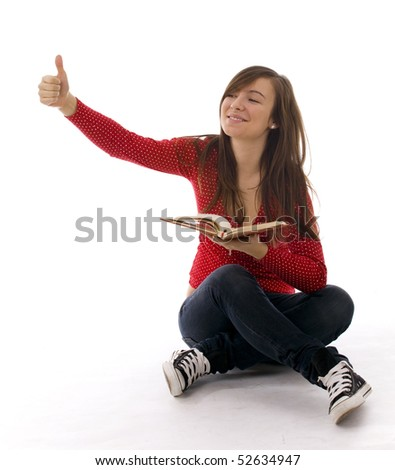 Sitting on the floor with crossed legs young woman keeping book and thumb up - stock photo
