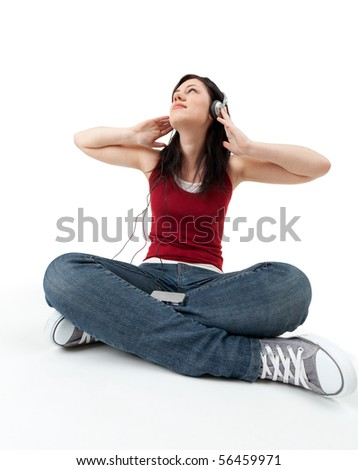 sitting on the floor young woman listening music from mp3 player - stock photo