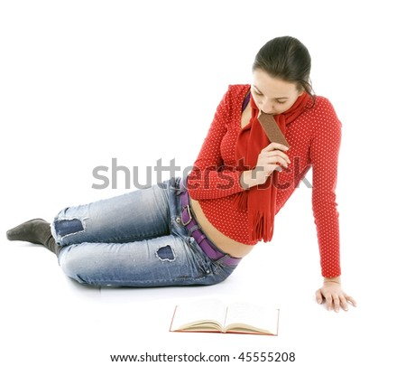 sitting on the floor young woman reading book and eating - stock photo