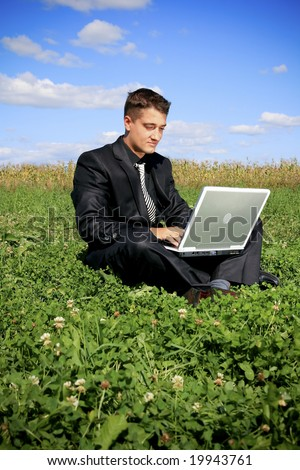 Sitting on the grass and typing - stock photo