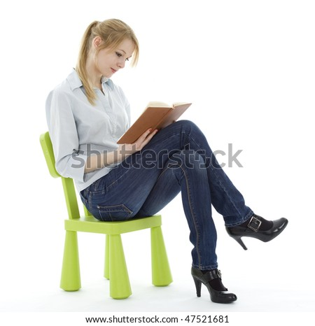 sitting on the green, child's chair young woman reading book - stock photo