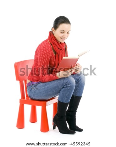 sitting on the red, child's chair young woman reading book - stock photo