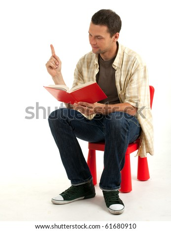 sitting on the small, red chair young man reading book