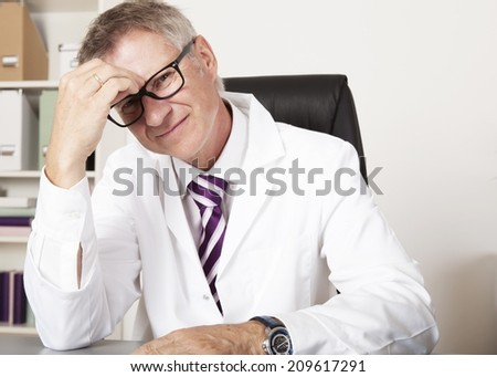Sitting Physician Having Headache looking at Camera