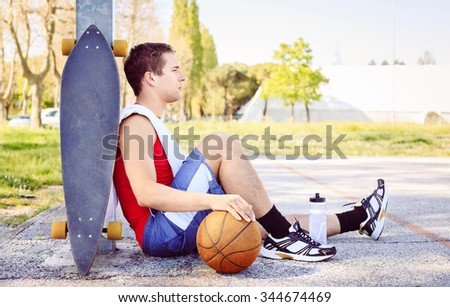 Sitting sportsman in a basketball court after match with friends. Blond guy searching concentration for doing sport in park. Concept of fitness training and jogging workout with vintage filter - stock photo
