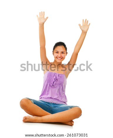 Sitting teenage girl while rejoices with arms up on white background - stock photo