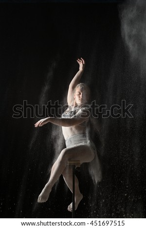 Sitting woman doing gymnastic element while sprinkled flour - stock photo